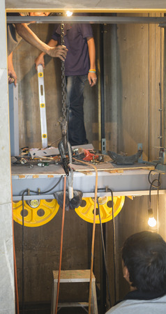 Technicians are installing a new elevator in the building to replace the old elevator was broken.