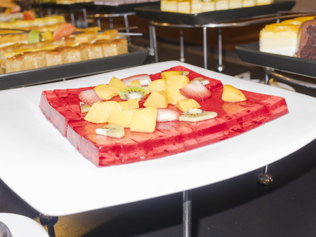 cold red jelly cake with many kind of fruits on buffet menu