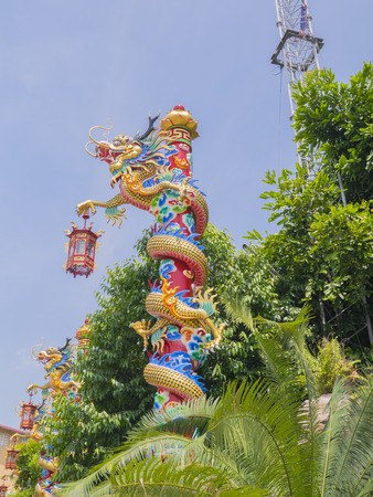 Chinese dragon around red column in blue sky Imagens