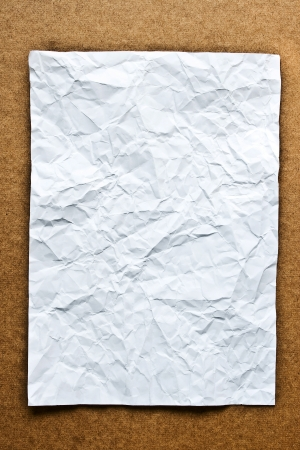 Crumpled paper on wood background photo