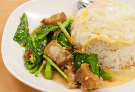 Fried kale with crispy pork and fried egg with cooked rice  Thai food  Close up photo