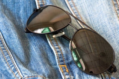 Aviator sunglasses isolated on blue jeans background photo