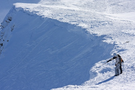 Two ski freeriders are standing on the brink of a precipice.  photo