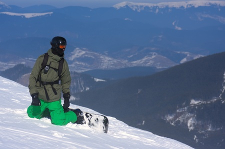 The snowboarder-freerider is sitting on the brink of a precipice.