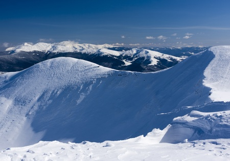 chasm: View from the top of the snow-capped mountain range. Ukraine, Dragobrat ski resort, Carpathian mountains. Stock Photo