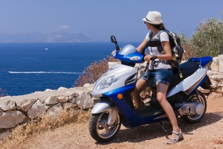 Young woman on a scooter is looking at the boats on blue Mediterranean sea.