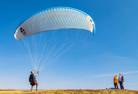 Kyiv oblast / Ukraine - April 09, 2020: Two spectators are watching as a paraglider is raising his blue wing up in the sky, ready to take off. Editorial
