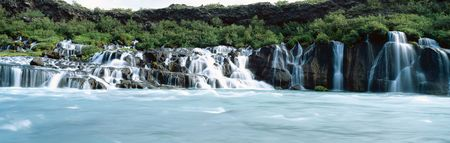 River Hvita sends glacial water flowing through layers of lava field at Hraunfossar waterfall Iceland Europe