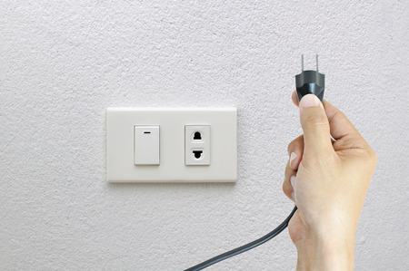 electrifying: Hand putting plug or unplug on socket and white wall background