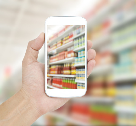 furtherance: Hand holding mobile on Supermarket blur background Stock Photo