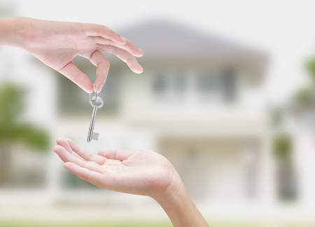 real estate background: Hand holding key on white background Stock Photo