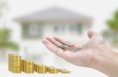 hands holding house: Hand holding key and gold coin on house background Stock Photo