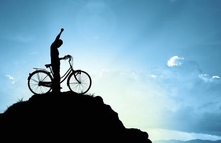 escalando: El hombre y la bicicleta en la montaña en la luz del sol Foto de archivo