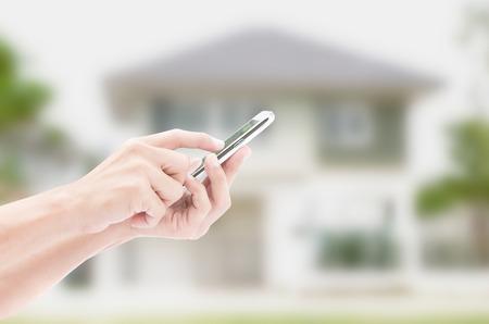 planificacion familiar: Mano que sostiene el tel�fono inteligente en las casas fondos Foto de archivo