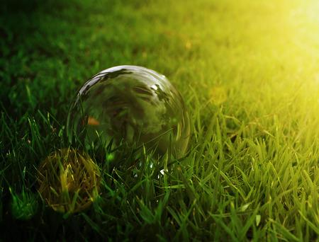 Glass ball on green grass in sunset dark light