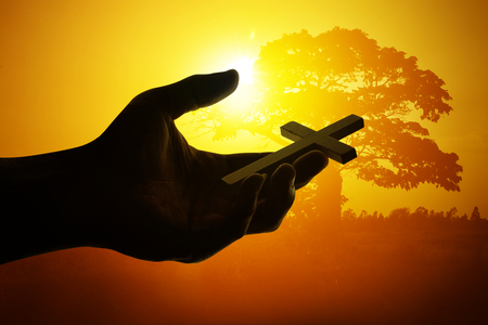 Silueta de la mano que sostiene la cruz