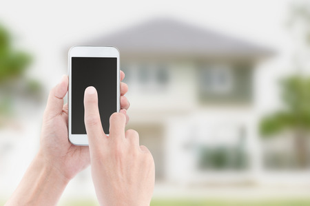 Hands holding and touch screen of smart phone on house backgrounds