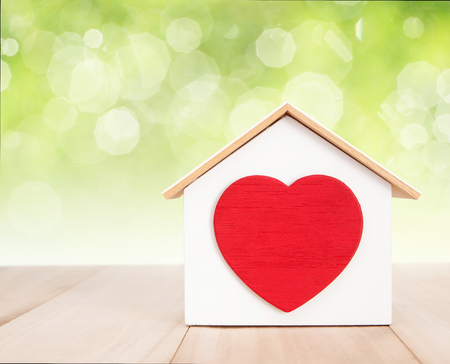 abstract heart: Home and red heart on wood with bokeh background