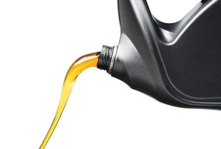 Pouring oil lubricant motor car from gray bottle on isolated white background Stockfoto