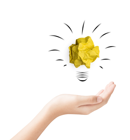 Female hand holding yellow paper crumpled lightbulb shape  isolated on white background idea business achievement education concept