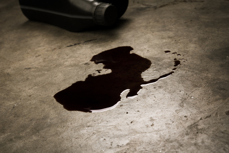 Old oil of car motor engine used spill on concrete floor and bottle