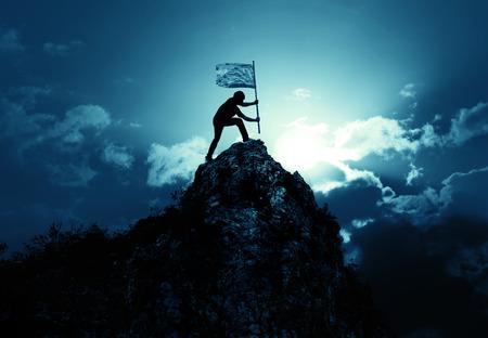 Hombre que sostiene la bandera en el pico de la montaña y el amanecer al aire libre en la naturaleza, el éxito del éxito concepto de negocio Foto de archivo - 81863268