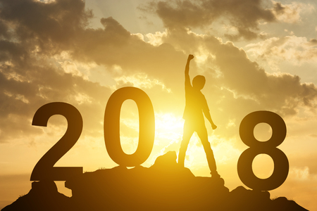 Man hand up on the peak of mountain and sunlight  with text 2018 sign happy new year calendar holiday concept