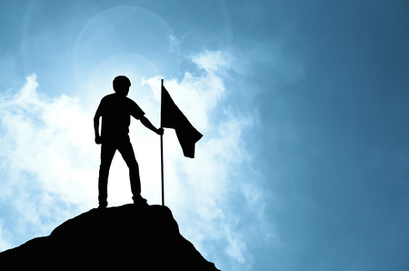 Man holding flag on peak of mountain and sunlight , success,winner, leader concept
