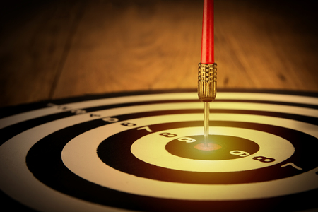 Dart arrow hit target center on wood table,aiming to dartboard goal business accuracy target,success,growth, concept  Stockfoto