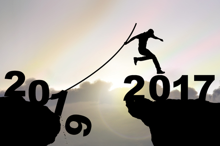vaulting: Man jumping over precipice with pole vault on Iridescence sky background , business people success happy new year 2017 concept