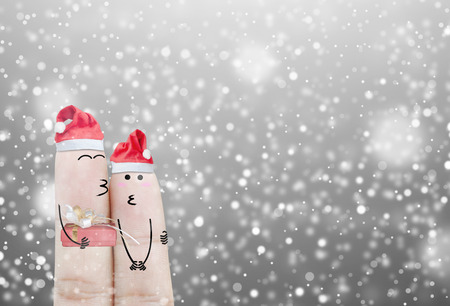 Couple finger with hat santa claus and gift on hand with snow holiday christmas art abstract background Stock Photo