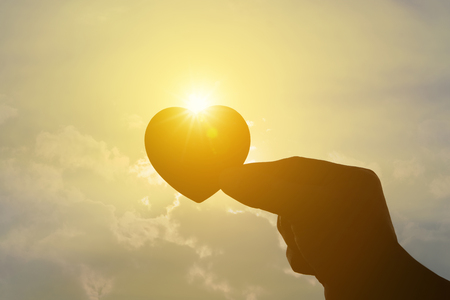 l hand: Silhouette hand holding heart on sunset and sky background freedom travel love vanlentine day concept Stock Photo