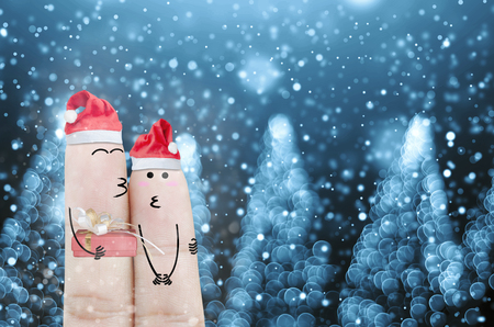 wedded: Couple finger with hat santa claus and gift on hand with snow holiday christmas art abstract background Stock Photo