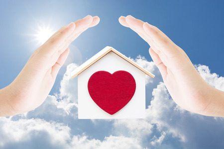 Two hands female protect house and red heart on blue sky clouds sun light background , home building landmark concept