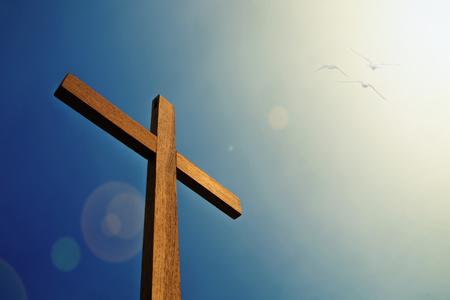 Kruis met vogel en zonlicht blauwe hemel Stockfoto