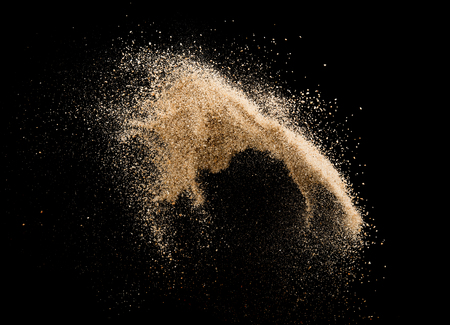 Sand flying explosion isolated on black background ,throwing freeze stop motion object design Standard-Bild