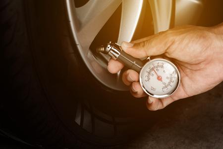Hand of man holding gauge measurement pressure checking tire of car transportation