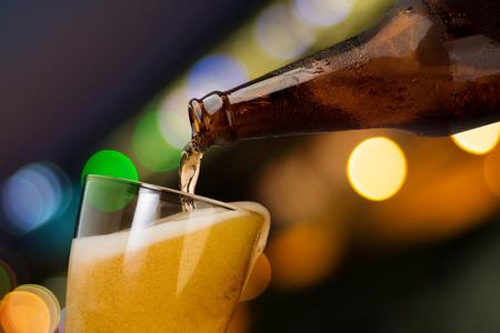 Bewegung des Bieres, das aus der Flasche in Glas auf Bokeh-Licht-Nachthintergrund gießt, trinkt Alkohol-Feierkonzept-Design Standard-Bild