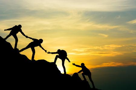 Gruppe von Menschen beim Bergsteigen auf dem Gipfel, die dem Team bei der Arbeit mit Sonnenuntergang helfen, Reise-Trekking-Erfolgsgeschäftskonzept