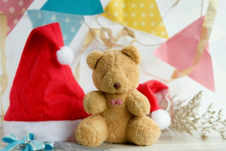 Teddy bear gift, on wood table, with Santa claus red had, flowers, pastel flags, happy new years conc. Foto de archivo - 111569601