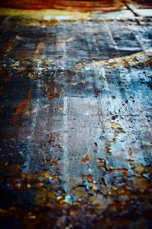 Metal floor with a shabby colourful covering photo