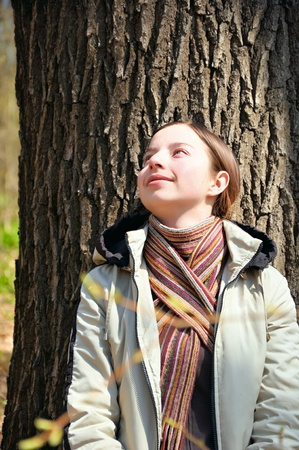 The beautiful girl in a scarf near a tree photo