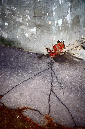 Crack in asphalt passing in the broken corner of the house photo