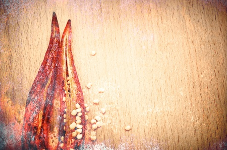 Background in grunge style. Peppers with grains on the wooden board