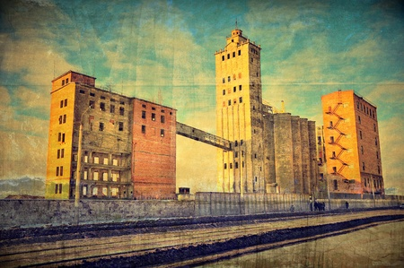 The thrown factory. The dilapidated building is connected to a tower the bridge. A background in style grunge Stock Photo - 12407680