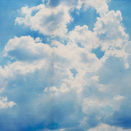 clouds on a textured vintage paper background, with grunge stains photo