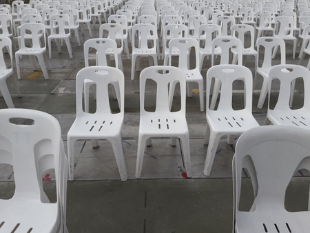 Row of white plastic chairs.