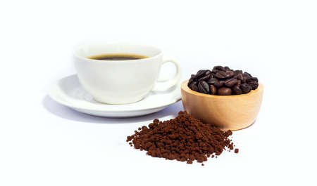 Closeup of coffee bean in wooden bowl and coffee powder with black coffee in white cup. isolated on white