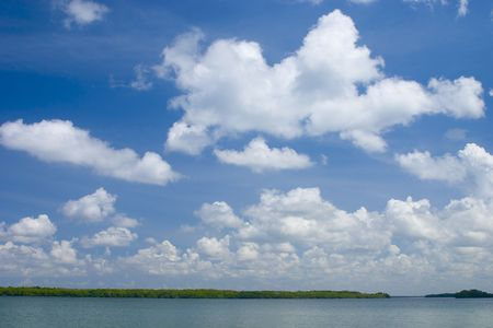 A blue, clouded sky hovers over tropical mangrove islands and open water