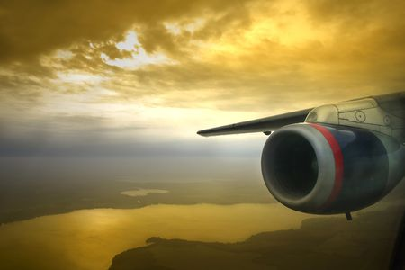 luxery: View of jet engine and wing a few thousand feet over the ground during sunset